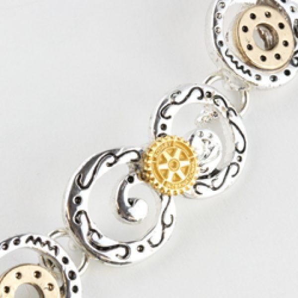 Sølv- og gullfarvede sirkler satt sammen med Rotary-logoer til armbånd.